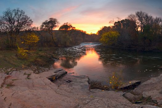 Colorful sunrise over the river with bright clouds. Autumn landscape