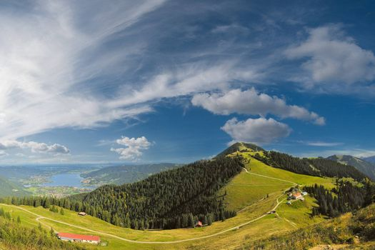 Beautiful panorama Alps mountains with lake in valley and clouds on background