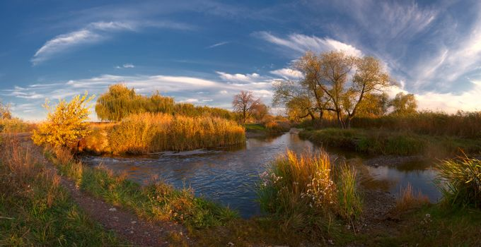 Colorful autumn landscape on evening river with majestic clouds. Panorama