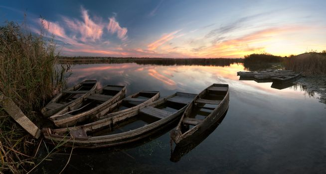 Evening colorful landscape with boats on the river and majestic sky reflection in the water