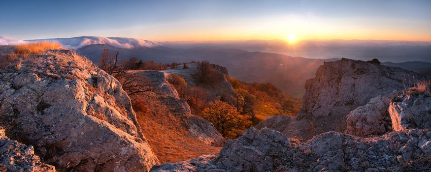 Sunrise panorama in the mountain, first sun rays through clouds