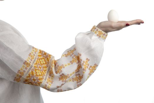 Woman's hand holding the egg. Traditional Ukrainian dress. Isolated on white