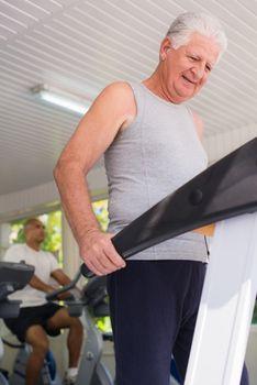 senior man exercising in wellness club