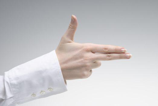Woman's hand showing pistol symbol