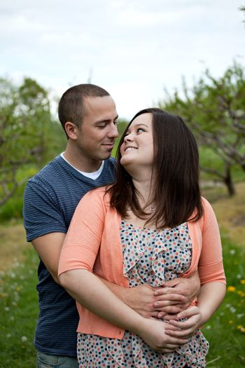 Young happy couple enjoying each others company outdoors walking through an orchard.