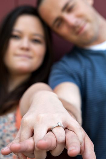 Young happy couple holding hands and showing the diamond engagement ring.  Shallow depth of field with strongest focus on the ring.