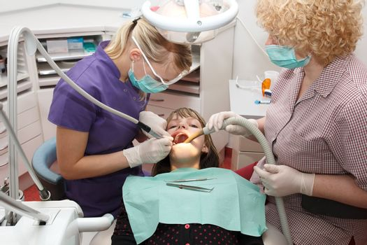 dentist with  assistant treats  a young girl teeth