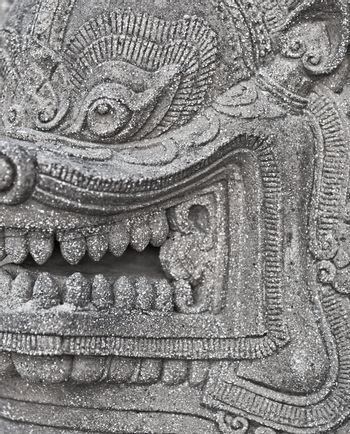 The stone head of an ancient Buddhist deity close-up