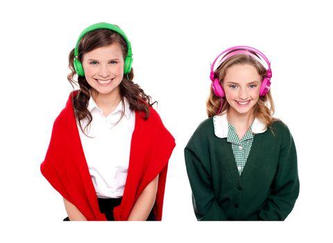 Schoolgirls listening music through headphones