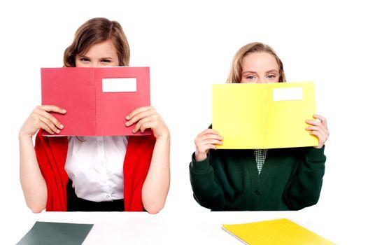 Naughty schoolgirls hiding behind the book