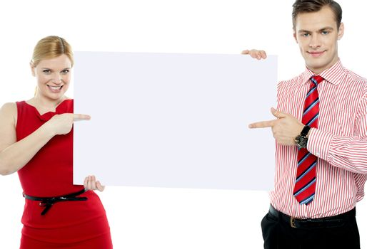 Business colleagues pointing at blank signboard