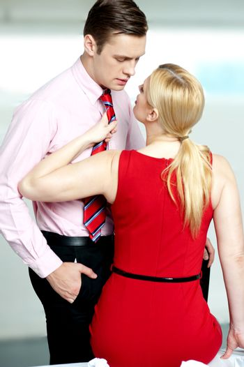 Woman pulling man from his tie. Feeling naughty