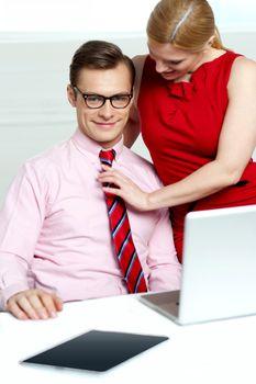 Female adjusting her co-workers tie
