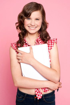 Joyful teenage girl holding spiral notebook