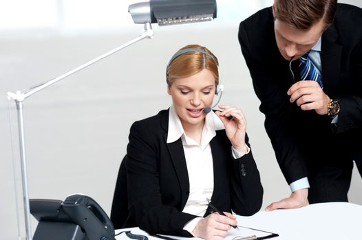 Woman discussing problem with male colleague