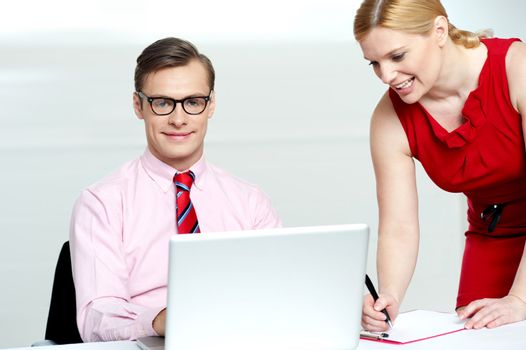 Woman writing information from laptop