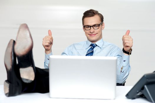 Relaxed businessman gesturing thumbs up