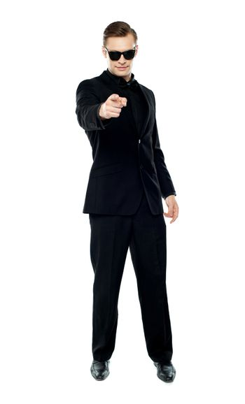 Man in party wear attire pointing at camera
