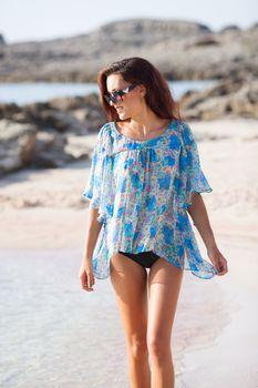 Young beautiful woman having fun on the beach waring blue shirt