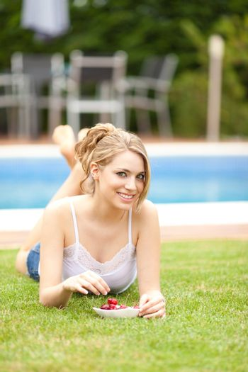young beautiful blonde girl eating cherries on the grass
