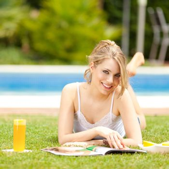 young beautiful blonde girl reading a magazine and drinking orange juice on the grass