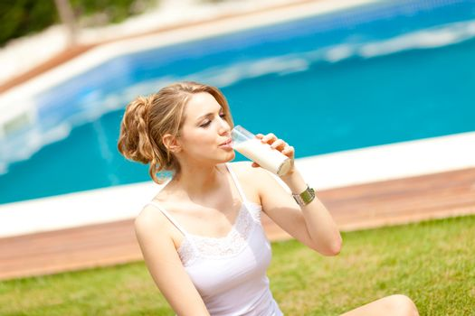 beautiful young women sited on the grass drinking a glass of milk