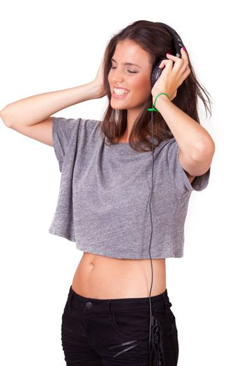 young beautiful women listening music on headphones, on white background, while laughing