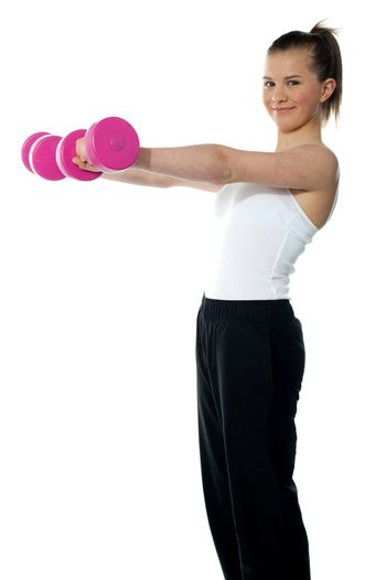 Pretty teenager working out with dumbbells