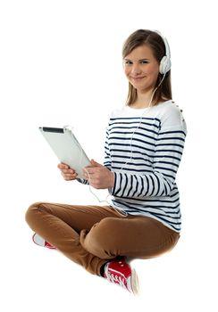 Seated girl enjoying music on portable device