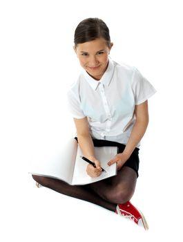 Aerial view of charming schoolgirl doing homework