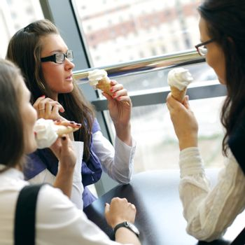 happy smiling women on foreground licking ice cream