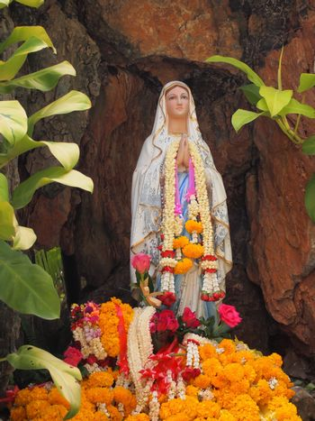 Virgin mary statue with garlands in cave.