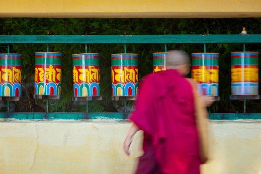Buddhist monk rotating prayer wheels in McLeod Ganj