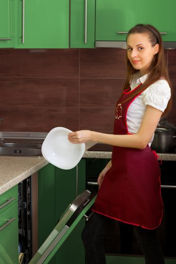 Housewife washing the dishes with the dishwasher