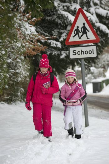 Children walking to school along a snow covered road