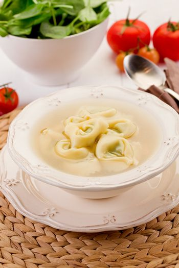 delicious tortellini pasta in broth with vegetables on white table