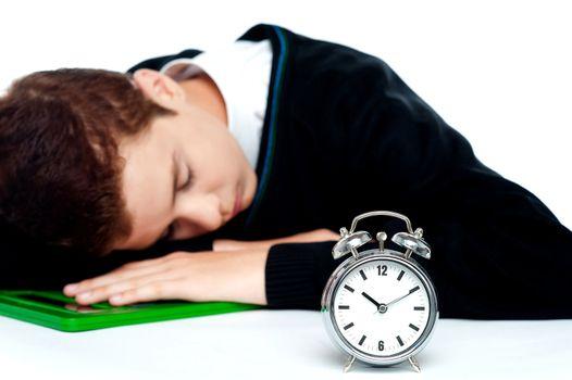 Tired schoolboy sleeping on calculator