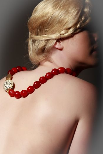 Blonde woman in covert act with a romantic hairstyle and designer necklace