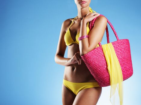 Sexy girl with pink bag and yellow bikini