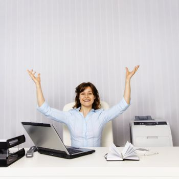 Happy young woman in the office workplace