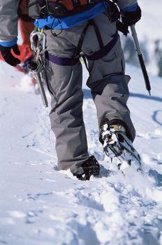 Young man mountain climbing on snowy peak