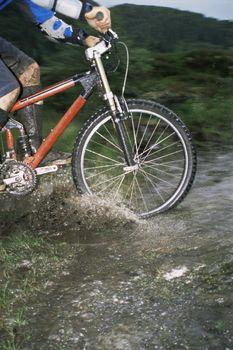 Mountain biker crossing stream