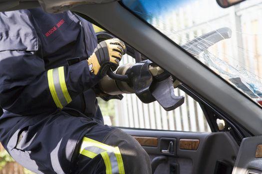 Firefighters breaking a car windscreen to help a car crash victi