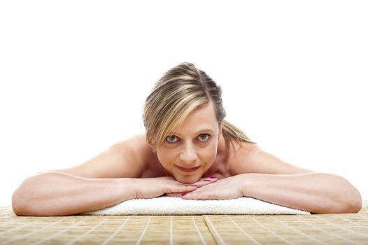 Matured naked woman lying on mattress