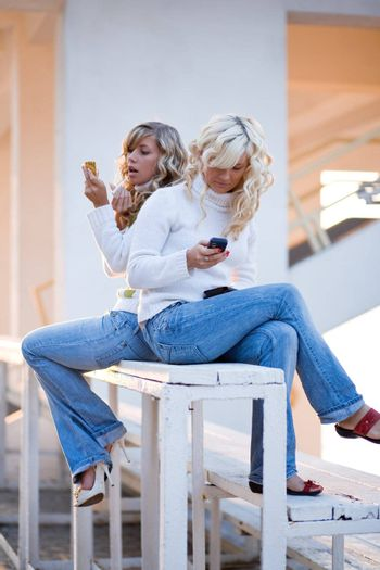 Two teenage girls sit and talking watching mobile phone.