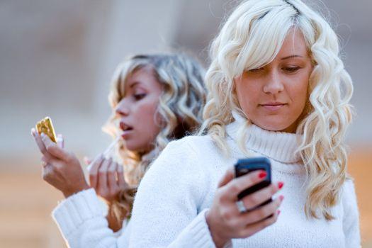 Two teenage girls sit and talking watching mobile phone.