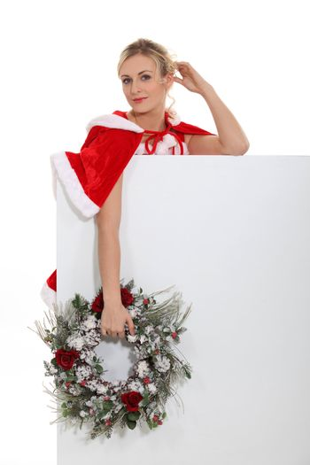 alluring mother Christmas holding garland standing behind copyspace