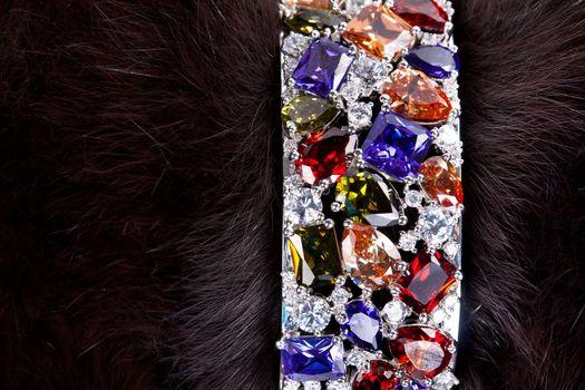 bracelet with precious stones in a dark fur