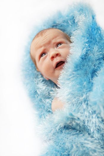 Infant baby wrapped in blue knited clothing