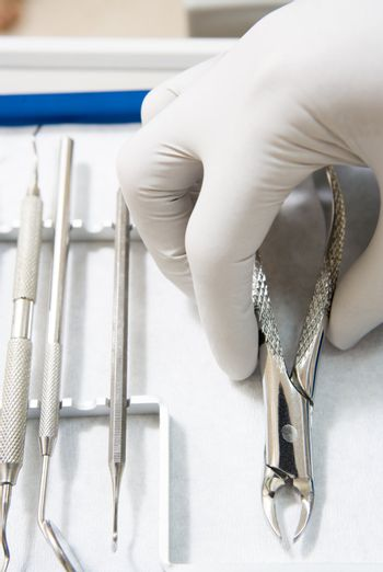 Dental tools with a gloved hand